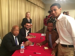 "Tanika Spates' children receiving a copy of ""March: Book One,"" signed by co-authors Rep. John Lewis and Andrew Aydin"